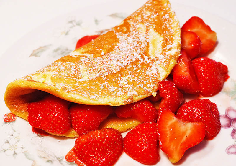Omelet souffle with strawberries and powder sugar