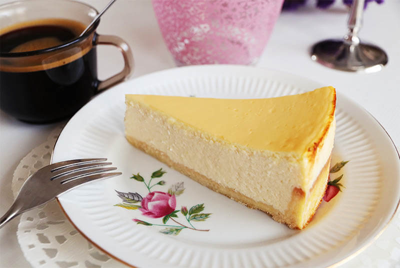 A slice of classic New York cheesecake on a plate with a cup of coffee.