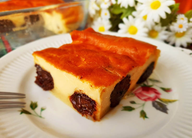 Far Breton, custard pie slice with rum prunes on a dessert plate.